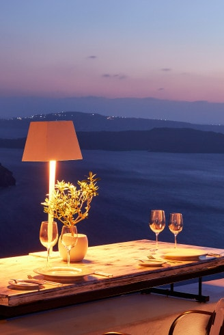 Table prepared for a private dining meal with a sunset sea view at San Antonio Hotel in Santorini