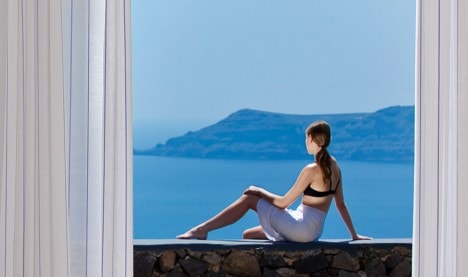 A woman sits on a wall at San Antonio Hotel in Santorini, admiring the view of the sea & the caldera