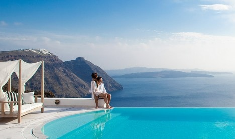 A couple enjoy the sea view from the pool at San Antonio wedding & honeymoon hotel in Santorini