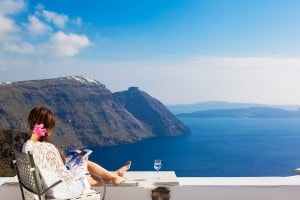 A woman reads her book on a Caldera sea view balcony at San Antonio Santorini hotel in Imerovigli