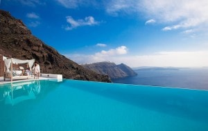 Couple relax on a sofa beside the San Antonio Santorini Hotel infinity pool overlooking the sea