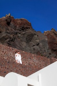 A couple on their honeymoon at San Antonio Santorini luxury Hotel admire the spectacular views