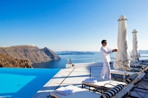 San Antonio Hotel staff member ties a sunbed umbrella beside the sea view infinity pool in Santorini