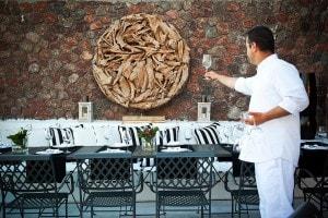 A waiter inspects wine glasses at the San Antonio Santorini Hotel Cliffside Dinner Restaurant