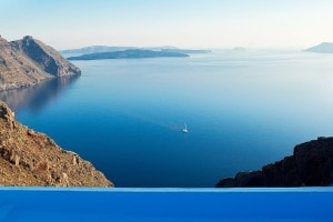 San Antonio luxury Hotel infinity pool overlooking Santorini caldera & a yacht sailing the sea