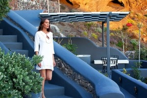 A woman walks down steps towards an outdoor seating area at San Antonio Luxury Hotel in Santorini