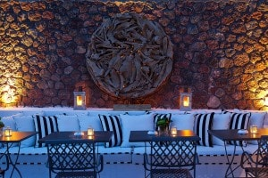 Sofa, tables & candles at the romantic Cliffside Dinner Restaurant at San Antonio Santorini Hotel