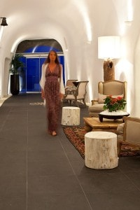 A lady walks through the elegant lobby cave passageway at San Antonio luxury Hotel in Santorini