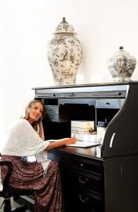 A lady uses the luxury writing desk bureau furniture at San Antonio Hotel in Imerovigli, Santorini