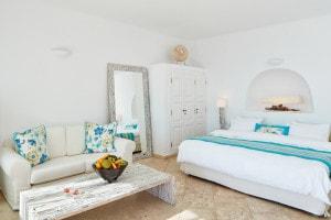 Stylish whitewashed cave bedroom of San Antonio luxury Hotel Honeymoon Suite Sea View in Santorini