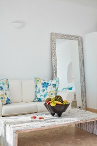 Sofa, coffee table, fruit & mirror in the San Antonio Hotel Honeymoon Suite Sea View in Santorini