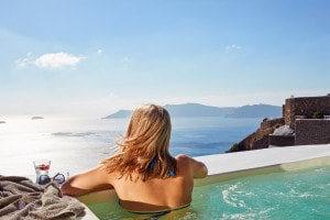 Guest enjoys Santorini caldera sea view from Honeymoon Suite outdoor Jacuzzi at San Antonio Hotel