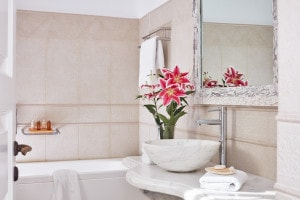 Flowers, washbasin, mirror & bath in San Antonio Hotel sea view Junior Suite bathroom in Santorini