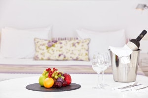 Bottle of wine & fruit on a table ready to be enjoyed in San Antonio Santorini Hotel Suite Sea View