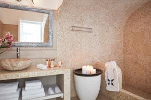 Suite Sea View tiled bathroom with candles at San Antonio Luxury Hotel in Imerovigli, Santorini