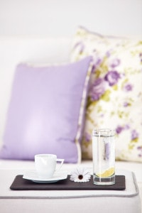 Coffee cup & water glass on a tray in front of cushions in the luxury Suite Sea View in Santorini