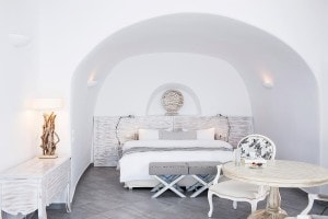 Bed, chairs, table & sideboard in cave bedroom of San Antonio Santorini luxury Hotel Suite Sea View