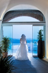 Bride in wedding dress framed by doors at San Antonio Santorini Luxury Hotel with a sea view behind