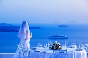 Wedding at San Antonio Hotel in Santorini. Bride holds wine glass by a table & looks at the sea view