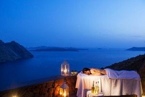 Woman lies on outdoor spa massage table at San Antonio Hotel overlooking the sea & Santorini caldera