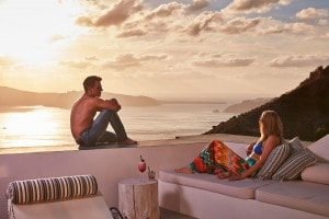 A glamorous couple relax & admire the sunset sea view from the bar at San Antonio Santorini Hotel