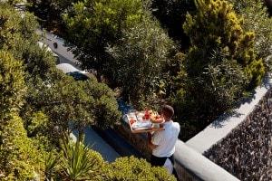 San Antonio Santorini Hotel waiter carries tray & delicious dessert from Cliffside Dinner Restaurant