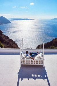 Man relaxes on a luxury sofa on a panoramic sea view balcony at San Antonio Santorini Hotel