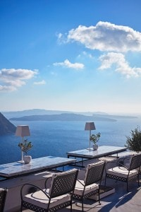 Dining tables & chairs at San Antonio Santorini Hotel restaurant bar offering a view of the sea