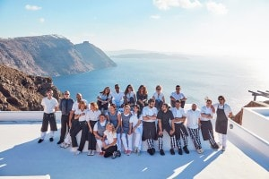 San Antonio luxury Hotel staff pose for a photo in front of a view of the sea & Santorini caldera