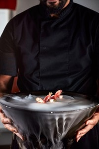 Waiter holds dry ice bowl with prosciutto rolls dish at Cliffside Dinner Restaurant in Imerovigli