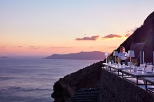 Waitress lays tables at Cliffside Dinner Restaurant in Santorini. Sunset over the sea behind.