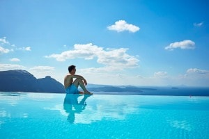 Man sitting on the edge of the San Antonio Hotel infinity pool in Santorini, admiring the sea view