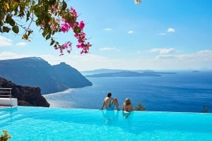Man & woman on the edge of the San Antonio Hotel infinity pool in Santorini, looking at the sea view