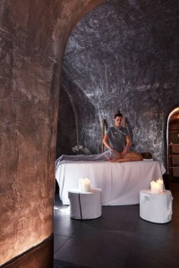 Lady enjoys spa massage treatments surrounded by candles in San Antonio Hotel cave spa in Santorini