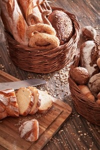 Board, knife, & baskets of fresh bread at Cliffside Dinner Restaurant at San Antonio Santorini Hotel