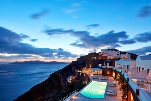 Dusk in Santorini. Sunset over the sea & the lights of San Antonio Hotel & the lighted infinity pool