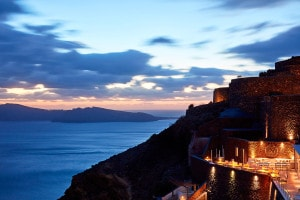 Lights illuminate San Antonio Luxury Hotel in Imerovigli, Santorini, as the sun sets over the sea
