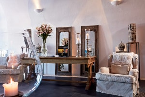 Luxury armchairs, desk, mirrors & furniture in a public area of the San Antonio Hotel in Santorini.