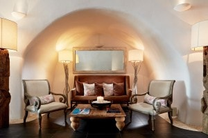A cave lounge area with chairs & a sofa at San Antonio luxury Hotel in Imerovigli, Santorini.