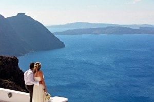 Husband & wife look at the view of the sea after a luxury wedding at San Antonio Hotel in Santorini