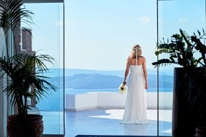 Bride stands on the Santorini caldera sea view balcony after her wedding at San Antonio Luxury Hotel