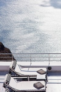The sunbeds in the infinity pool area at San Antonio Santorini luxury Hotel offer a great sea view