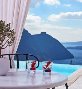 Cocktails on table overlooking San Antonio Santorini Hotel infinity pool & a view of the sea
