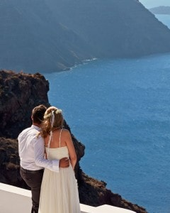 Bride & groom admire the sea view after wedding at San Antonio Santorini luxury Hotel in Imerovigli