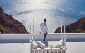 Man admires Santorini Caldera & sea view from private veranda of San Antonio Hotel Honeymoon Suite