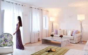 Lady opens curtains to look at the sea view from the lounge area of the Honeymoon Suite in Santorini