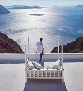 A man looks out at the sea view from the San Antonio Santorini caldera hotel in Imerovigli