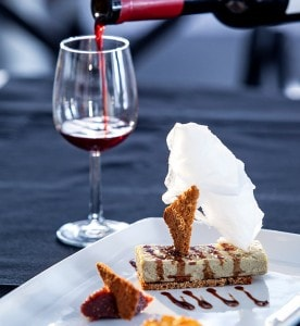Romantic private dining with a dessert & a glass of red wine at San Antonio Hotel in Imerovigli