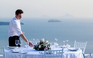 Waiter prepares wedding reception dining table at San Antonio Santorini weddings Hotel in Imerovigli