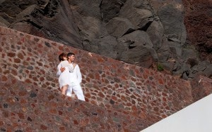 Newly married couple standing on the Caldera cliff at San Antonio Santorini weddings hotel.